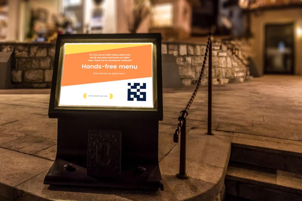 Digital signage display stand in front of restaurant with QR code for downloading digital menu