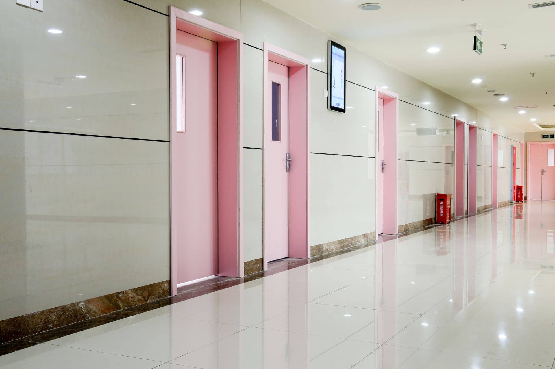 Hospital hall with digital way guidance system next to doors